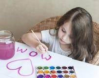 做自创贺卡的孩子 一个小女孩绘在一张自创贺卡的心脏作为一件礼物为母亲节 免版税库存照片
