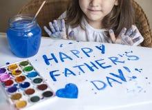 做自创贺卡的孩子 一个小女孩绘在一张自创贺卡的心脏作为一件礼物为父亲节 库存照片