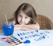 做自创贺卡的孩子 手画 一个小女孩绘在一张自创贺卡的心脏作为父亲的一件礼物 图库摄影