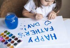 做自创贺卡的孩子 手画 一个小女孩绘在一张自创贺卡的心脏作为父亲的一件礼物 免版税图库摄影