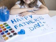 做自创贺卡的孩子 手画 一个小女孩绘在一张自创贺卡的心脏作为父亲的一件礼物 免版税库存照片