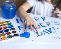 做自创贺卡的孩子 手画 一个小女孩绘在一张自创贺卡的心脏作为礼物 免版税库存图片