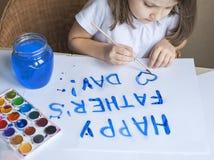 做自创贺卡的孩子 手画 一个小女孩绘在一张自创贺卡的心脏作为礼物 图库摄影