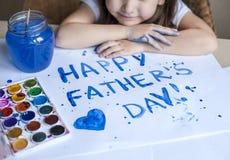 做自创贺卡的孩子 手画 女孩绘在一张自创贺卡的心脏作为一件礼物为父亲节 免版税库存图片
