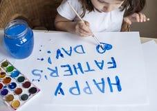 做自创贺卡的孩子 手画 女孩绘在一张自创贺卡的心脏作为一件礼物为父亲节 免版税库存照片