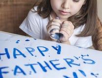 做自创贺卡的孩子 手画 女孩绘在一张自创贺卡的心脏作为一件礼物为父亲节 库存图片