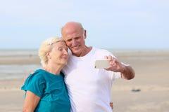 做自已照片的资深夫妇在海滩 免版税库存图片