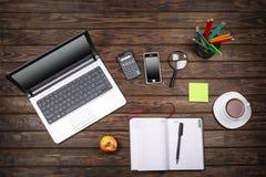 做自由职业者的概念,企业概念,办公室桌书桌,膝上型计算机,空的笔记本,咖啡,智能手机,计算器,木ba 免版税库存图片