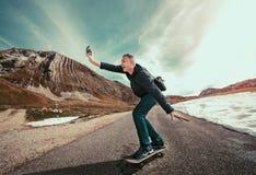 做自由职业者获得的商人乐趣,当驾驶滑板时 免版税图库摄影