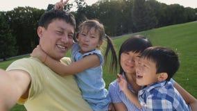 做自画象的愉快的亚洲家庭在电话 影视素材