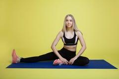 做舒展在一张蓝色瑜伽席子的白肤金发的女孩 库存照片