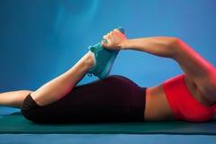 做舒展在一张蓝色瑜伽席子的运动的女孩 健身、体育、训练、人们和生活方式概念 库存图片