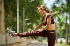 做舒展在体育前的妇女训练在早晨3 免版税图库摄影