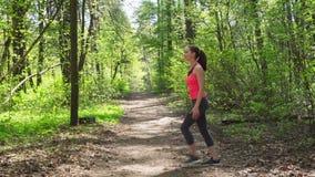 做舒展在奔跑前的妇女在森林里 股票视频
