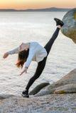 做舒展在岩石的年轻女人 库存图片