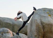 做舒展在岩石的年轻女人 免版税库存图片
