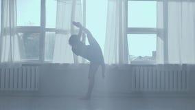 做舒展在背后照明的窗口附近的亭亭玉立的女孩 股票录像