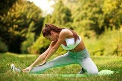 做舒展的女孩在公园,健身行使户外 免版税库存图片