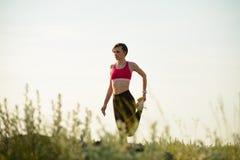 做舒展的妇女室外 准备锻炼在夏天晚上 体育和健康活跃Lifesyle概念 库存图片