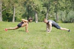 做舒展的妇女行使与个人教练员在公园 库存照片