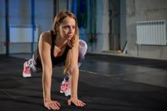 做舒展的灰色绑腿的美丽的肌肉女孩 炫耀在工业样式的健身房 库存图片