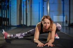 做舒展的灰色绑腿的美丽的肌肉女孩 炫耀在工业样式的健身房 免版税库存照片