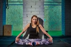 做舒展的灰色绑腿的美丽的肌肉女孩 炫耀在工业样式的健身房 免版税库存图片