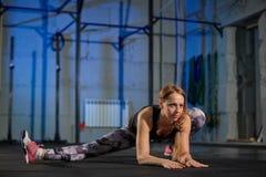 做舒展的灰色绑腿的美丽的肌肉女孩 炫耀在工业样式的健身房 免版税图库摄影