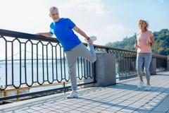做舒展的老人行使,当妇女跑步时 免版税库存图片