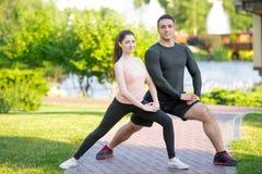 做舒展的运动的夫妇在公园在 免版税库存图片
