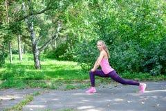 做舒展的运动的妇女画象在公园行使在训练前 女运动员为跑步做准备 库存照片
