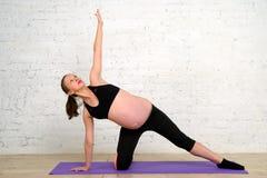 做舒展的年轻人孕妇在瑜伽席子行使 免版税库存图片