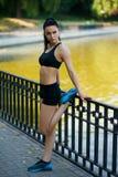 做舒展锻炼的赛跑者妇女 做腿筋舒展的运动的妇女外形画象在公园在跑步以后 免版税库存照片