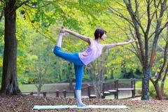 做舞蹈姿势的瑜伽阁下的日本妇女 图库摄影