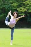 做舞蹈姿势的瑜伽阁下的日本妇女 免版税库存照片
