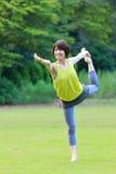 做舞蹈姿势的瑜伽阁下的日本妇女 免版税库存图片
