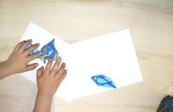 做艺术和工艺的孩子小组在幼儿园 孩子在日托中心的花费时间与巨大兴趣 免版税库存照片