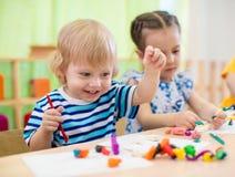 做艺术和工艺的愉快的孩子 开玩笑幼稚园 免版税库存图片