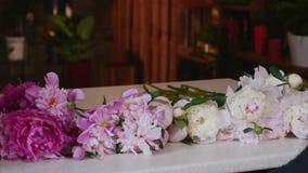 做花束的专业卖花人开始桃红色牡丹 库存照片