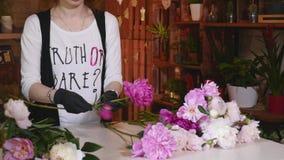 做花束的专业卖花人开始桃红色牡丹 免版税库存照片