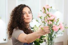 做花束的美丽的被集中的少妇卖花人在商店 免版税库存图片