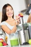 做苹果和蔬菜汁的妇女在榨汁器 免版税图库摄影
