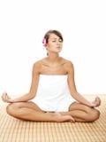 做莲花瑜伽姿势的俏丽的妇女在温泉 免版税图库摄影