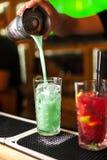 做蓝色、绿松石和红色鸡尾酒在酒吧的专家的侍酒者特写镜头 免版税图库摄影