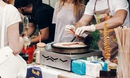 做薄煎饼的人在街道食物节日 烹调法语的厨师 图库摄影