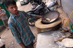 做薄煎饼的年轻人在streetside餐馆在德里, Indi 库存照片