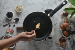 做薄煎饼,蛋糕,面包师的手烘烤的顶视图倾吐或挖出在平底锅上的面团 烹调成份的概念和 库存图片