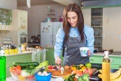 做蛋糕的愉快的少妇抹上层数与站立在厨房里的奶油 免版税库存图片