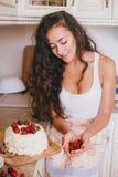 做蛋糕的年轻美丽的妇女在厨房 免版税库存照片