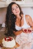 做蛋糕的年轻美丽的妇女在厨房 免版税库存图片